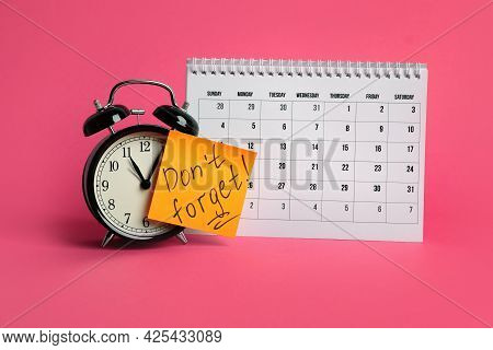 Alarm Clock, Calendar And Reminder Note With Phrase Don't Forget On Pink Background