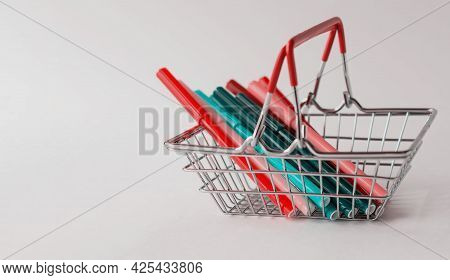 A Group Of Multicolored Markers In A Miniature Shopping Basket In A Supermarket, Close-up. Return To