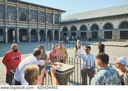 Tourist Group In A Courtyard Of Ulu Cami Or Grand Mosque. Guide Tells Visitors About Sundials At Mos