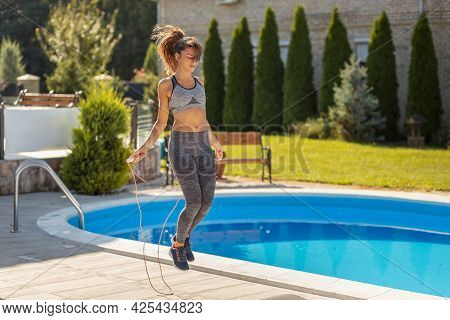 Young Fit Woman Doing Fitness Workout Outdoors, Exercising Using Jump Rope