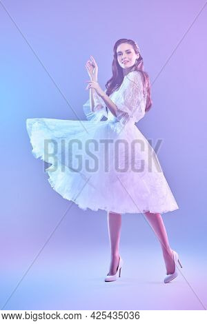 Wedding fashion. Full length portrait of a beautiful girl in a luxury white dress posing at the studio in gentle pink and lilac light. Beauty, fashion.