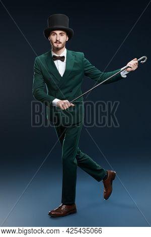 Men's fashion. Elegant gentleman in a suit and top hat dances with a cane. Studio portrait on a dark blue background.
