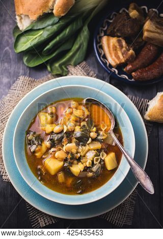 A Blue Bowl Of Spanish Chard Stew With Beans, Potatoes, Pork Belly And Chorizo In A Dark Setting