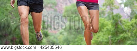 Runners legs banner crop of woman and man athletes running in nature outdoors background training cardio and strength. Panoramic view of lower body of jogging people.