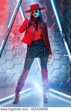 Full length portrait of a stunning fashion model girl in stylish leather clothes, red sunglasses and red hat posing among the neon lamps. Futurism, techno style.