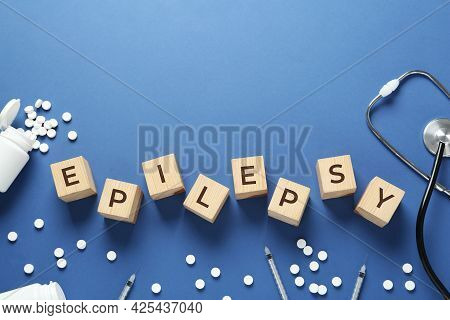 Wooden Cubes With Word Epilepsy, Stethoscope, Pills And Syringes On Blue Background, Flat Lay. Space