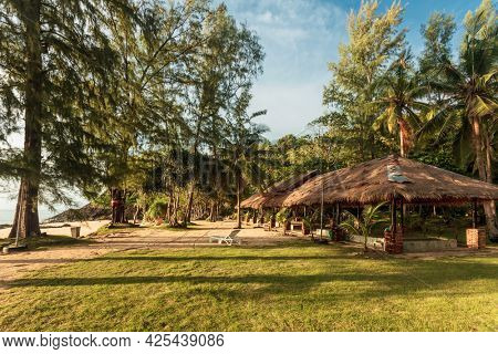 bungalows on a tropical beach in sunset light. Thailand