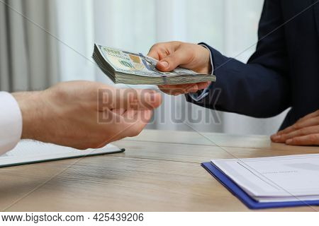 Cashier Giving Money To Businessman At Desk In Bank, Closeup