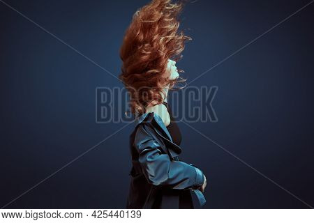 Professional modern style dancer dancing at studio on a dark blue background. Expressive dancer with flying hair.