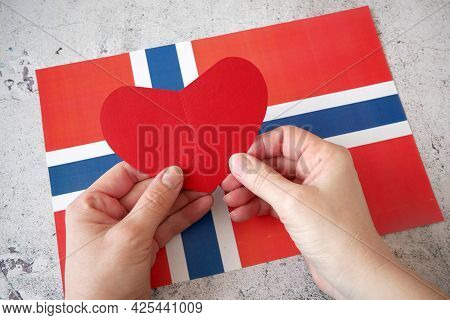 I Love Norway. Hands Puts Paper Red Heart On Norway Flag Background. Norway Constitution Day - 17 Of