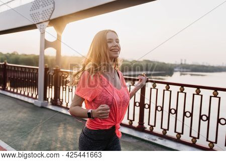 Excited Caucasian Woman Running In Morning. Good-humoured Sporty Girl Training With Smartwatch.