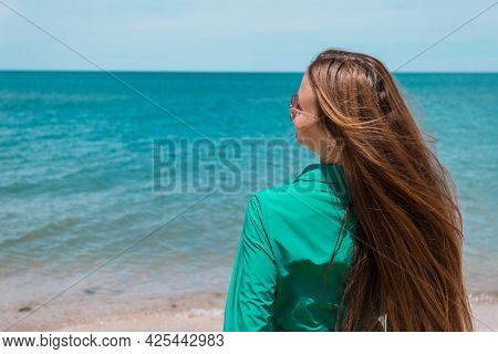A Girl With Long Hair In A Green Dress On The Beach. Beach Holidays