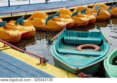 Rowboats And Pedal Boats Are Tied To The Pier. There Is A Lifebuoy Inside The Boat. Pier On The Lake
