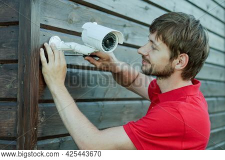 Caucasian Technician Installing Ip Wireless Cctv Camera By Screwed For Home Security System