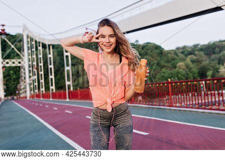 Shapely European Girl Enjoying Photoshoot After Marathon. Outdoor Photo Of Blissful Female Runner Po
