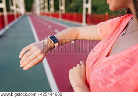 Slim White Girl Looking At Her Sport Wristwatch After Marathon. Outdoor Portrait Of Female Model In