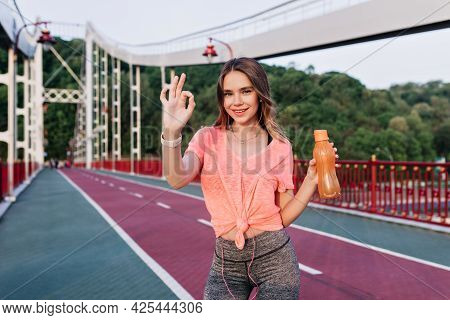 Active Fair-haired Girl Spending Time At Stadium. Cute Female Runner Posing After Marathon And Smili