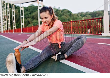 Good-humoured Female Runner Preparing For Marathon. Outdoor Portrait Of Ecstatic Girl Stretching Bef