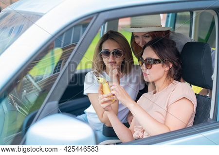 Three Happy Girlfriends Go On A Trip. Women Are Driving In A Car And Taking A Selfie On A Mobile Pho