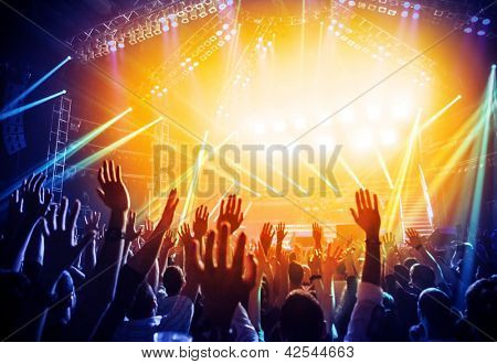 Photo of young people having fun at rock concert, active lifestyle, fans applauding to famous music band, nightlife, DJ on the stage in the club, crowd dancing on dance-floor, night performance
