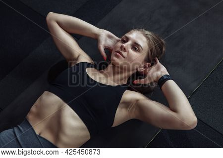 Young Fit Woman Trains Abdominal Muscles Lying On Floor In Gym
