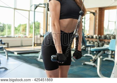Young Sexy Fit Woman With Perfect Body In Sportswear Trains Triceps In Crossover Cable Exercise Mach