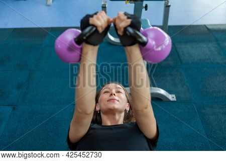 Young Fitness Woman Trains Pectoral Muscles With A Kettlebells In Her Hands While Lying On A Bench I