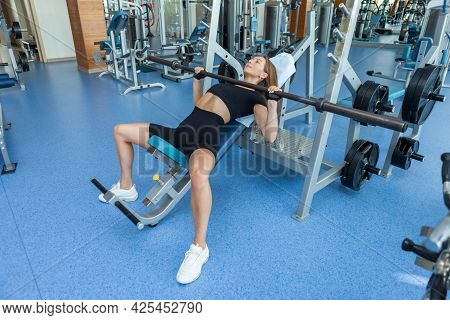 Young Fit Slim Woman In Sportswear Trains Pectoral Muscles Doing Incline Press In The Gym