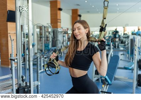 Beautiful Muscular Woman Posing With Suspension Strap System In Gym