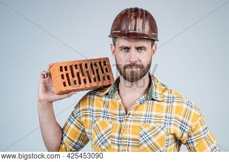 Man Bricklayer In Construction Helmet And Checkered Shirt On Building Site With Brick, Brickwork.