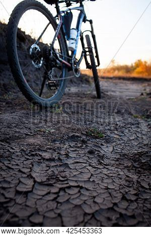 Blurred Bicycle On Dry Cracked Ground. Cracked Ground In Shallow Depth Of Field. Dirt Bike Riding. R