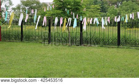 Decorations Made Of Colored Ribbons Tied To A Rope Along A Fence In A Summer Park, Garden Festive An