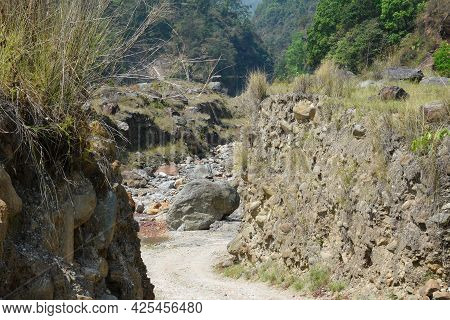 A Dusty Road Leading To Himalayan Rivulet.