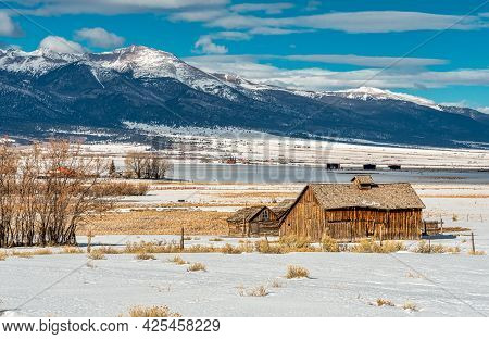 Several Beautiful Old, Weathered Cabins Beneath A Cold Winter Sky And Set Against The Grandeur Of Th