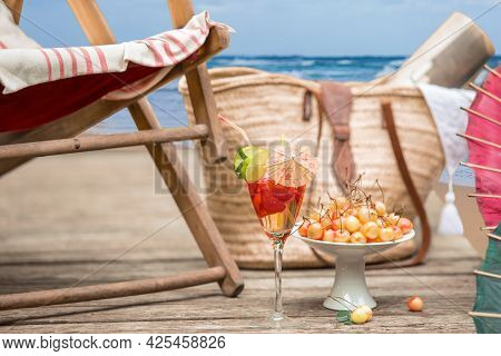 Set Of The Concept Of A Holiday By The Sea. Sun Chair, Fruit And Ice Cocktail, Wicker Bag And Readin