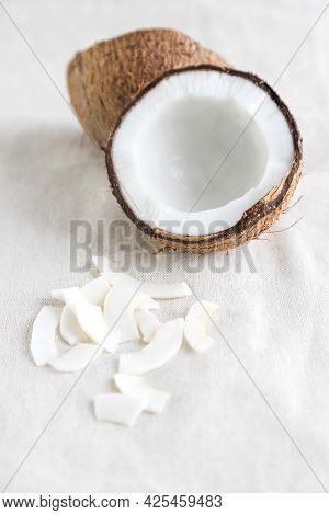 Coconut Chips On A Linen Tablecloth And Half Of A Fresh Coconut Nearby. A Healthy Snack Ideal For Nu