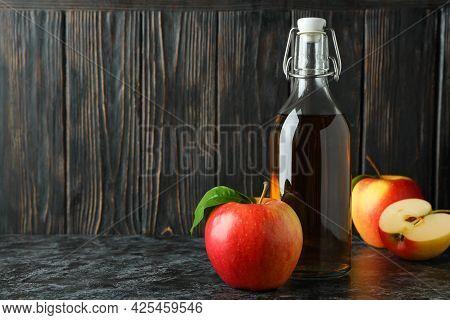 Homemade Apple Vinegar And Ingredients On Black Smokey Table
