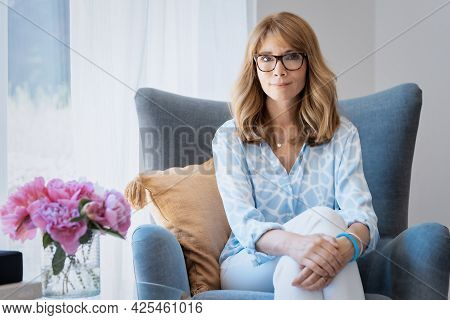 Attractive Woman Relaxing In The Armchair At Home
