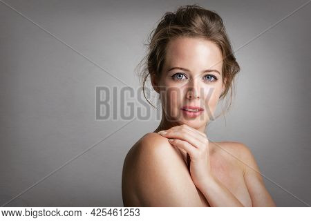 Close-up Beauty Portrait Of Gorgeous Woman Wearing Natural Makeup While Standing At Isolated Backgro