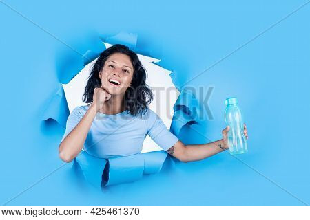Concept Of Sport Drinking. Girl On Blue Background. Joyful And Charming Smile. Student Girl Hold Wat