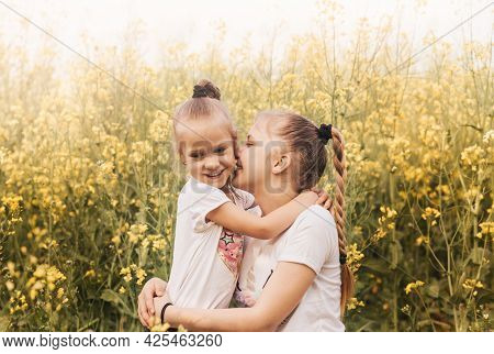 Two Little Girls Sisters Cuddle In Nature In Summer