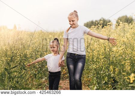 Two Little Sisters Walk Around The Flowering Canola In Summer. Two Little Sisters Hold Hands, Stand