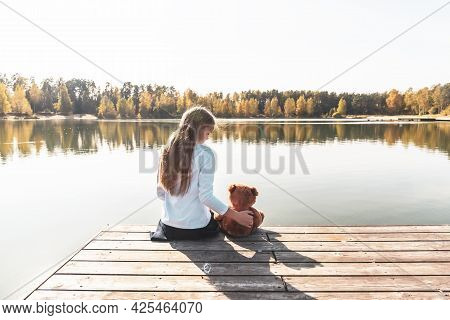 Long Haired Little Girl With Cute Teddy Bear Sits On Pier Near Wide River Against Autumn Forest On S