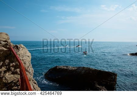 Boat With Passengers At Sea, Summer Vacation, Yacht Trip In The Middle Of Rocks And Mountains, Seasc