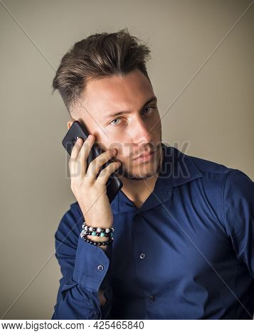 Handsome Young Man Talking On Cell Phone In Studio