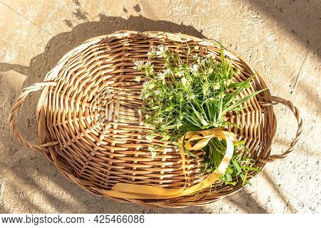 Elegant Wicker Tray With Handles And Bouquet Of Windflowers Tied With Golden Ribbon On Beige Table A