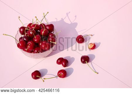 Fresh Juicy Cherries On A Pink Pastel Background In A Glass Bowl. Seasonal Berries And Fruits. Place
