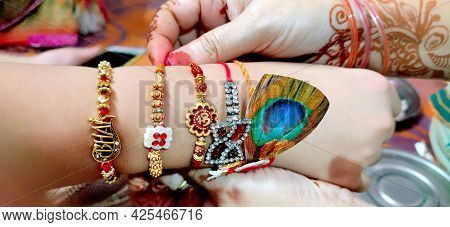 Hand Of A Lady Tying Rakhi In Hand Of A Guy During The Hindu Ritual Of Rakshabandhan With Selective