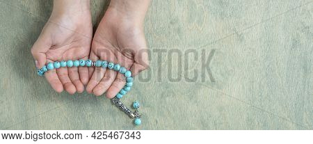 Hands Of Child Holding Rosary. Ramadan Kareem Background. Muslim Kid Holds A Rosary. Flat Lay. Copy