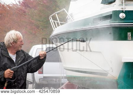 Caucasian Man Washing Boat Hull With Pressure Washer